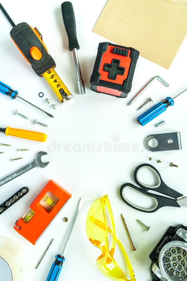 Bästa sikt av funktionsdugliga hjälpmedel, skiftnyckeln, skruvmejseln, nivån, måttbandet, bultar och säkerhetsexponeringsglas på  royaltyfria bilder