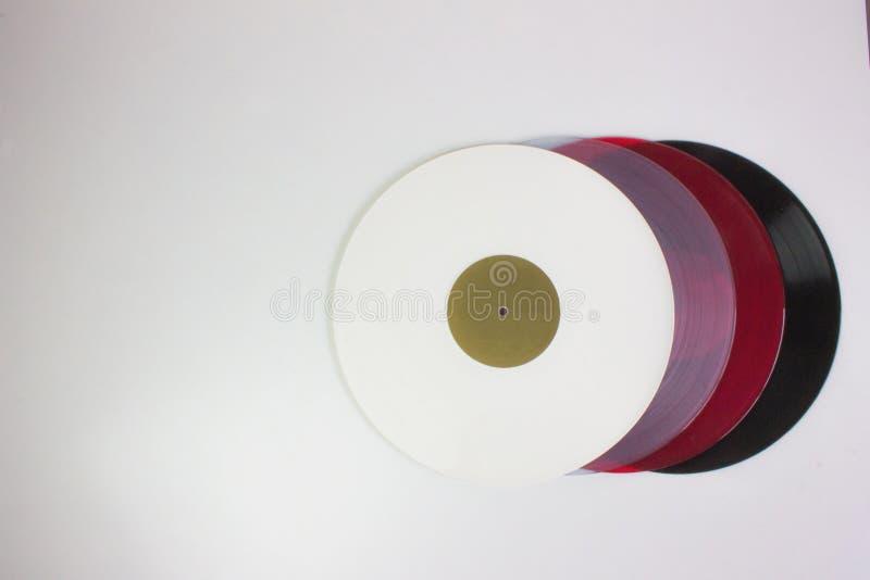Bästa sikt av fyra vinyler, svart, rött, blått och vitt, på vit bakgrund royaltyfria bilder