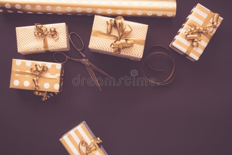 Bästa sikt av gåvaaskar i guld- designer Lekmanna- lägenhet, kopieringsutrymme Ett begrepp av jul, nytt år, födelsedagberöm arkivfoton