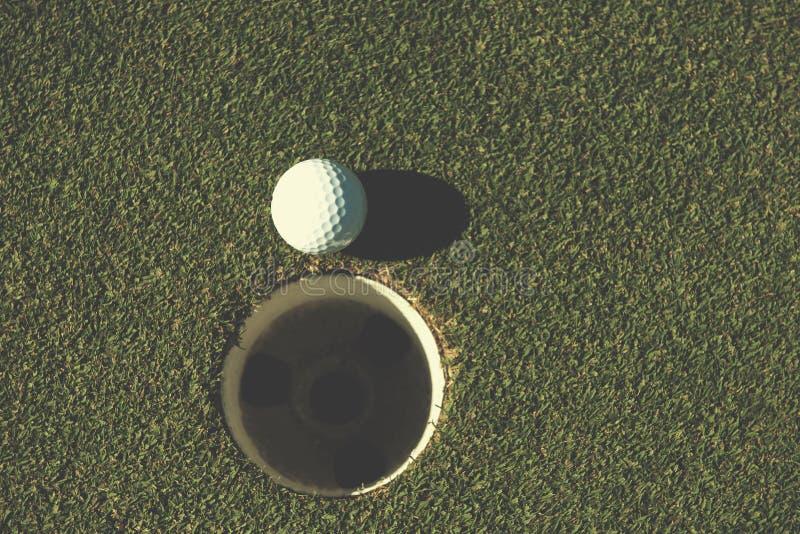 Bästa sikt av golfboll i hålet arkivbild
