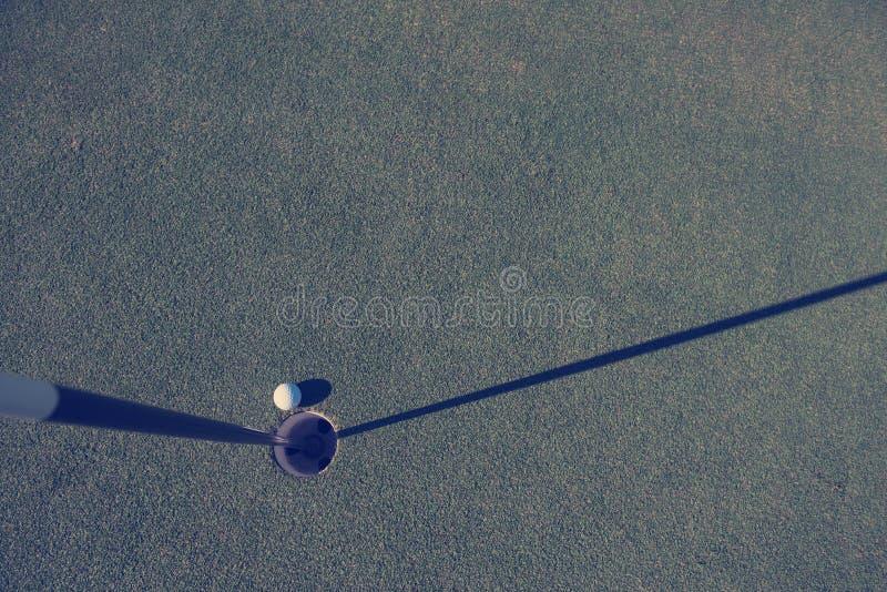Bästa sikt av golfboll i hålet royaltyfri foto