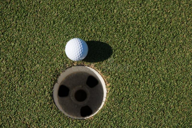 Bästa sikt av golfboll i hålet royaltyfri bild