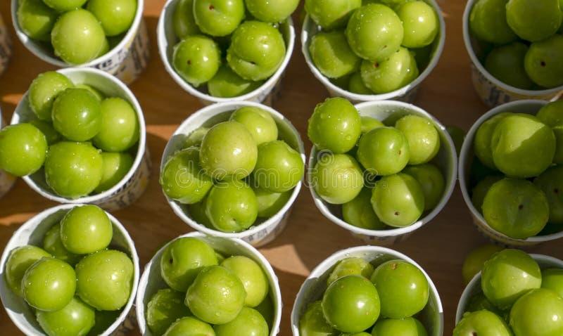 Bästa sikt av gröna plommoner eller renklon i pappers- kopp på försäljning i gatan i Turkiet, populära vårfrukter med ett mycket  royaltyfri fotografi