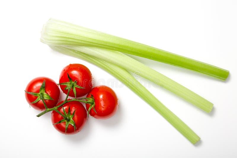 Bästa sikt av gruppen av nya tomater och selleripinnar arkivfoton