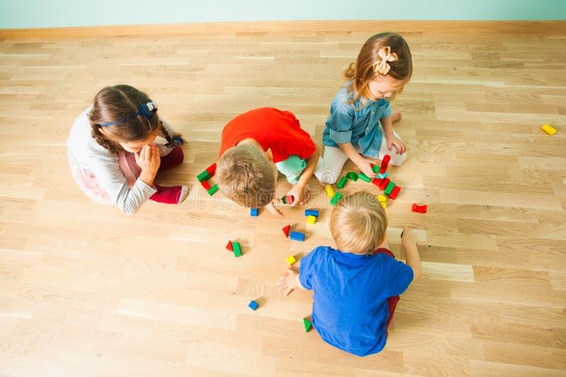 Bästa sikt av gruppen av barn som spelar på ett golv royaltyfria bilder
