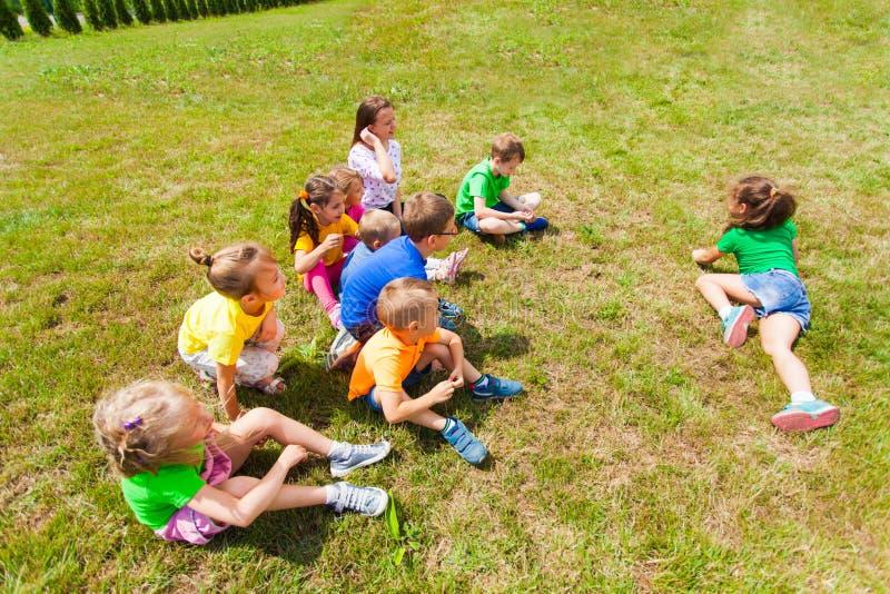 Bästa sikt av gruppen av barn som spelar på gräs royaltyfri bild