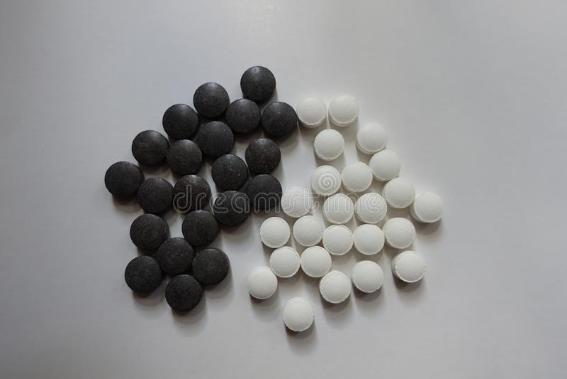 Bästa sikt av gruppen av svart chelated järn och vita piller för vitamin K royaltyfri fotografi