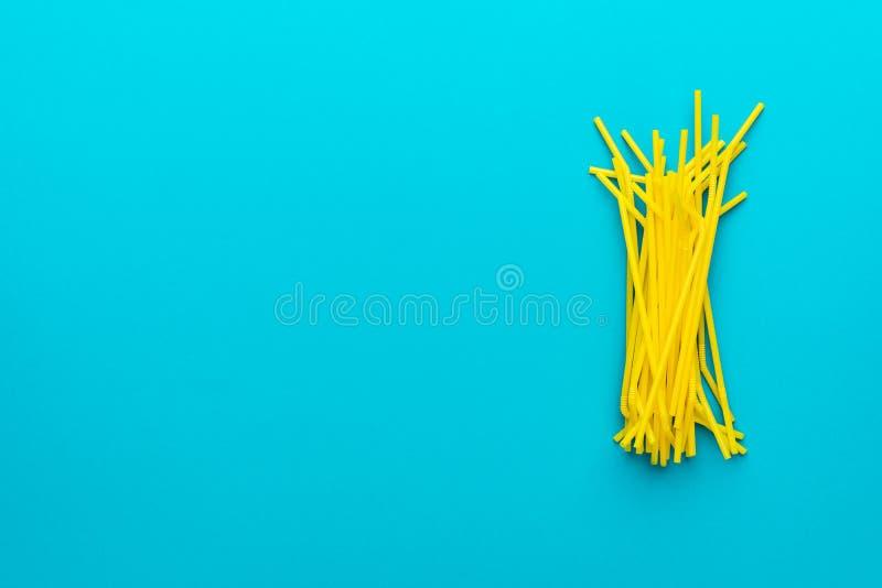 Bästa sikt av gula dricka sugrör över utrymme för turkosblå bakgrund och kopierings royaltyfri foto