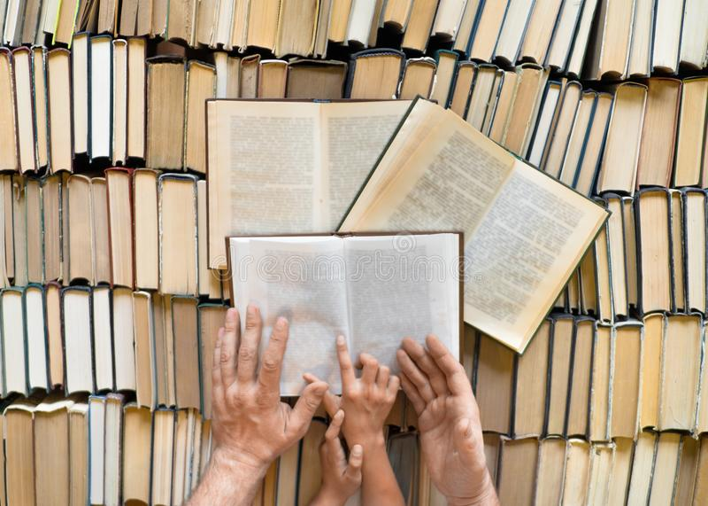 Bästa sikt av händer av en fader och en unge över många böcker arkivbild