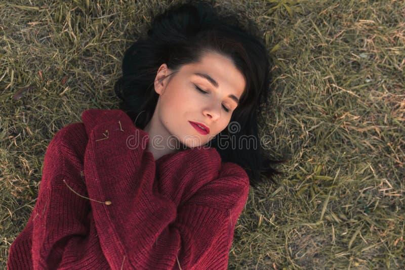Bästa sikt av härligt ungt Caucasian le för kvinna och stängda ögon, bärande stucken sweater som ligger på gräset arkivbild