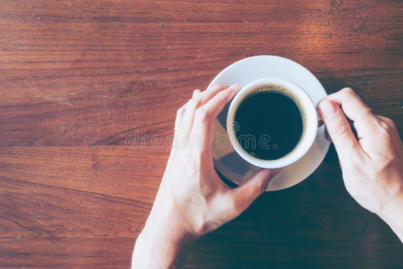 Bästa sikt av Hand& x27; s-manhåll per koppen av varmt kaffe på gammal träta fotografering för bildbyråer