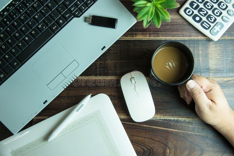Bästa sikt av handen för grafisk design för kontorsmaterial som rymmer en kaffecu fotografering för bildbyråer
