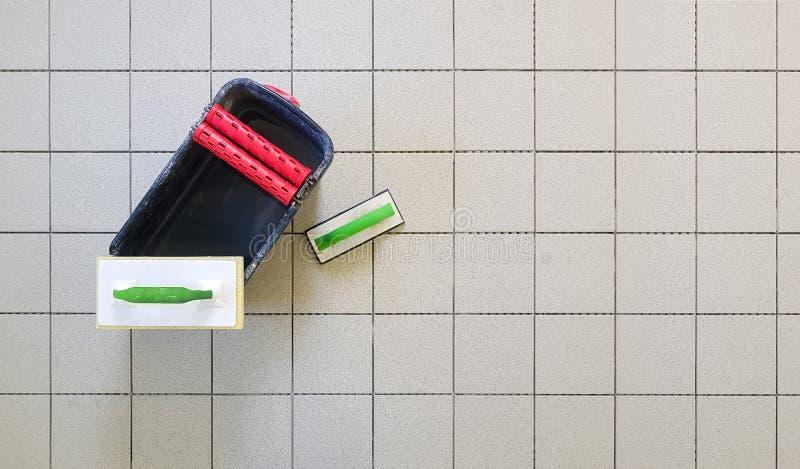 Bästa sikt av hjälpmedel för att grouting keramiska tegelplattor Tilers som använder en gummimurslev och svamp royaltyfri fotografi