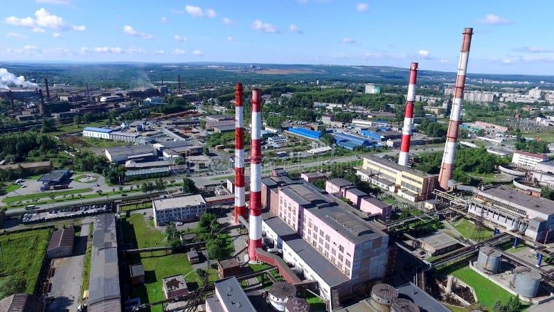 Bästa sikt av industriområde av staden och växten med röda och vita rör Panorama av staden med fabriker och växter arkivbilder