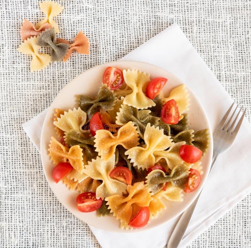 Bästa sikt av italiensk kulör pastafarfalle med basilika och tomater royaltyfria foton