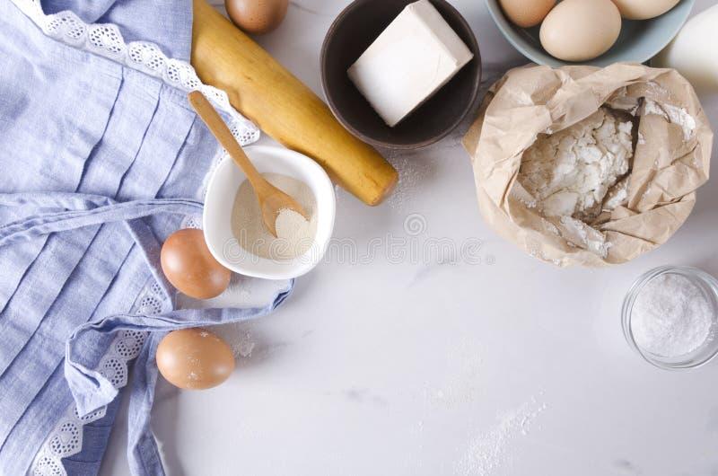 Bästa sikt av köksbordet, ingredienser för deg och framställning av bagerigods, produkter T?m utrymme f?r din text royaltyfria foton