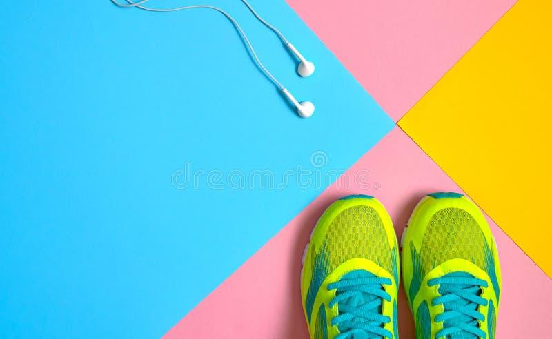 Bästa sikt av körande sportskor och hoppande over vita hörlurar på rosa, blå och gul pastellfärgad bakgrund, kopieringsutrymme fö royaltyfri fotografi