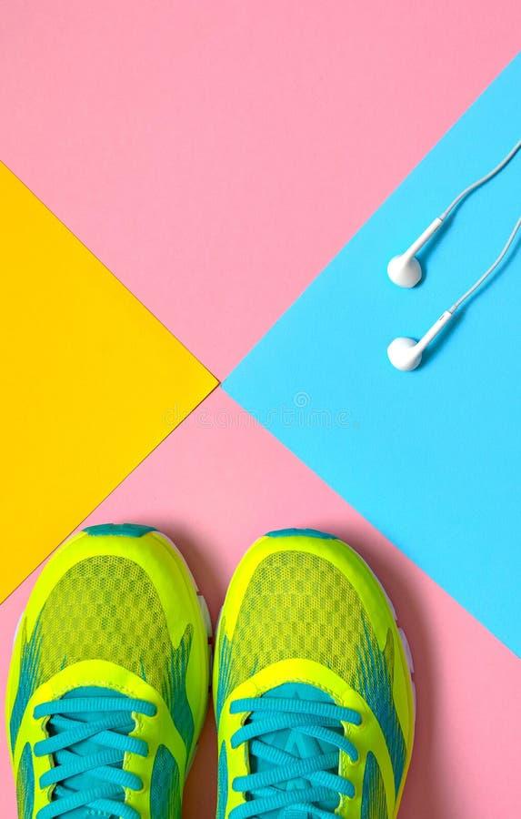 Bästa sikt av körande sportskor och hoppande over vita hörlurar på rosa, blå och gul pastellfärgad bakgrund, kopieringsutrymme fö royaltyfria foton