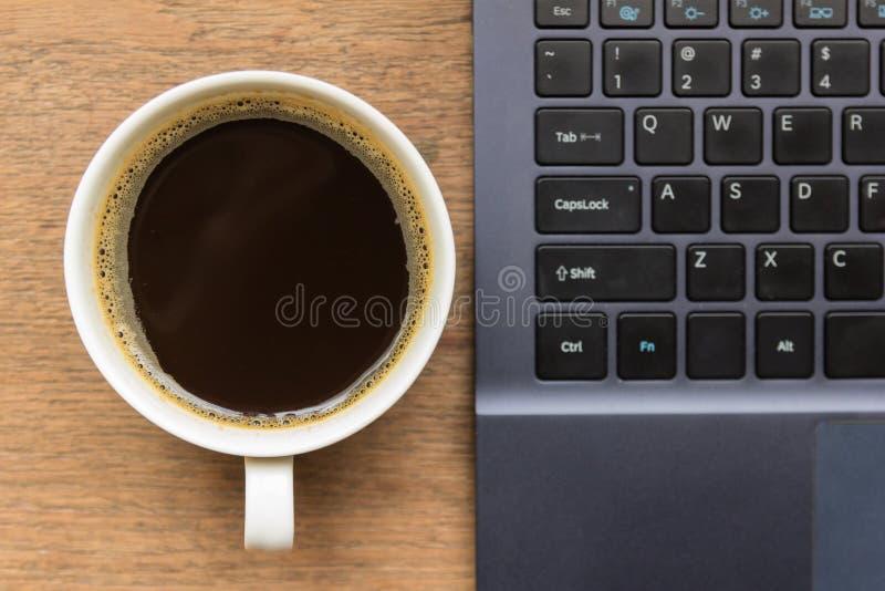 Bästa sikt av kaffekoppen, bärbar dator på trätabellen royaltyfri fotografi