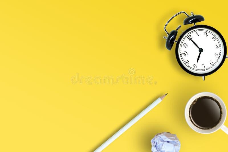 Bästa sikt av kaffekoppen, den vita blyertspennan, den retro ringklockan och det vita skrynkliga pappers- bollstället på gul floo royaltyfria bilder