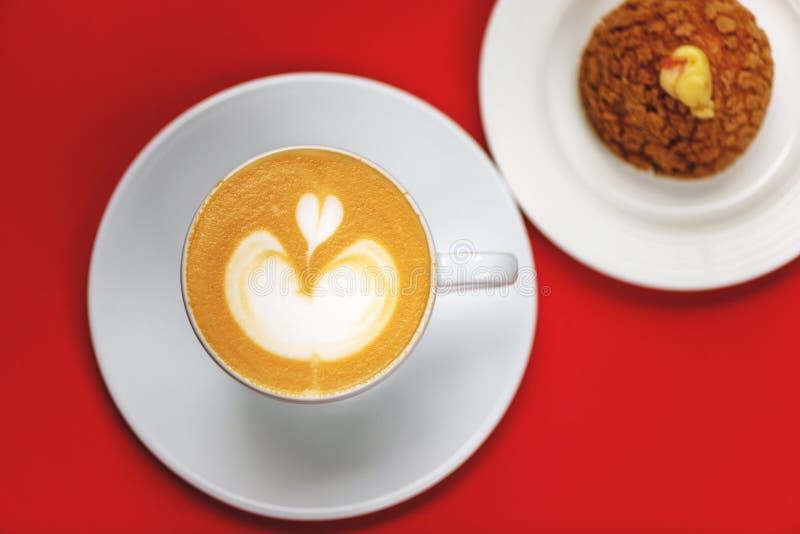 Bästa sikt av kaffekoppen med lattekonst och chouxbakelse royaltyfri bild