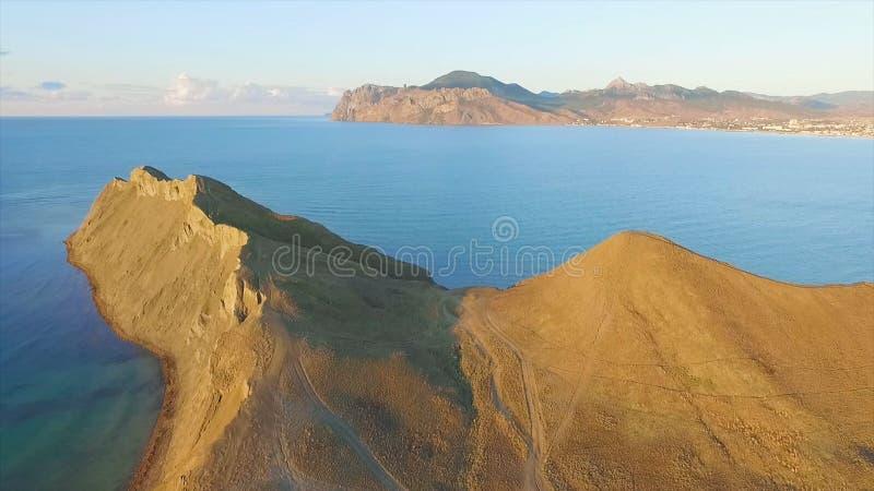 Bästa sikt av klippan vid havet skjutit Härlig sikt av bergområdet vid havet på solnedgången arkivfoton
