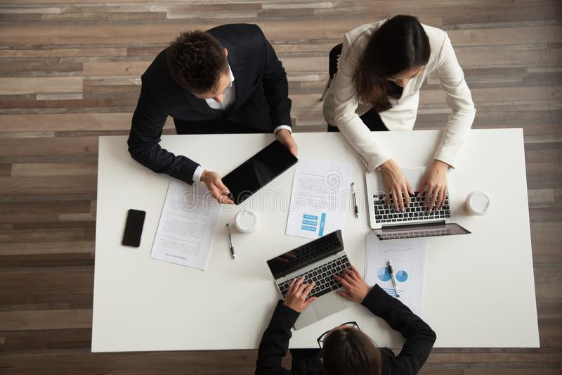 Bästa sikt av kollegor som i regeringsställning arbetar på bärbara datorer arkivbild