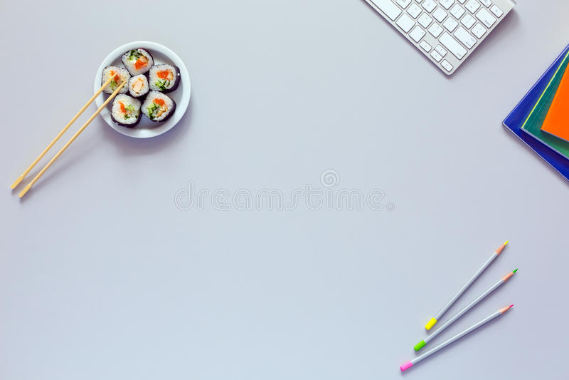 Bästa sikt av kontorsarbetsstället på det gråa skrivbordet med sushi royaltyfri bild