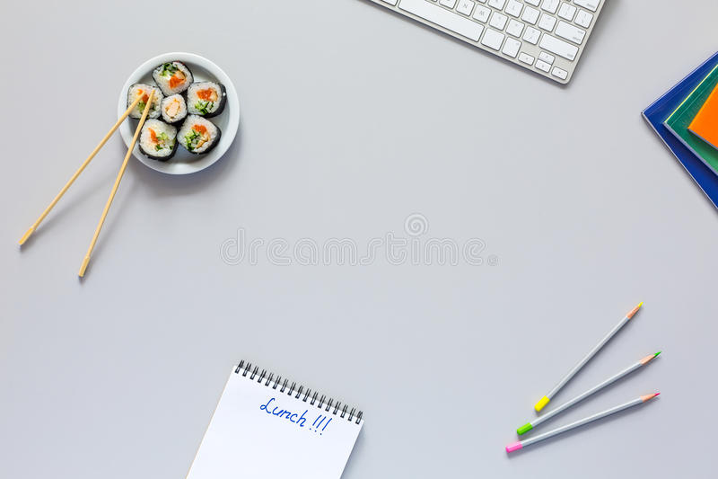 Bästa sikt av kontorsarbetsstället på det gråa skrivbordet med sushi arkivfoto