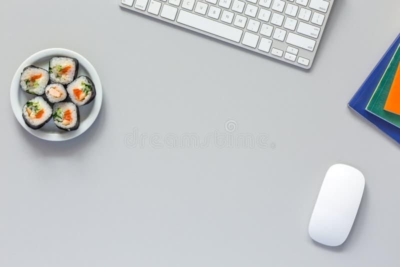 Bästa sikt av kontorsarbetsstället på det gråa skrivbordet med sushi royaltyfria foton