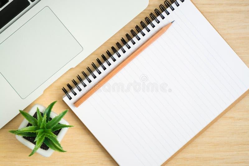 Bästa sikt av kontorsskrivbordet med den öppna spiralanteckningsboken på den wood tabellen royaltyfria bilder