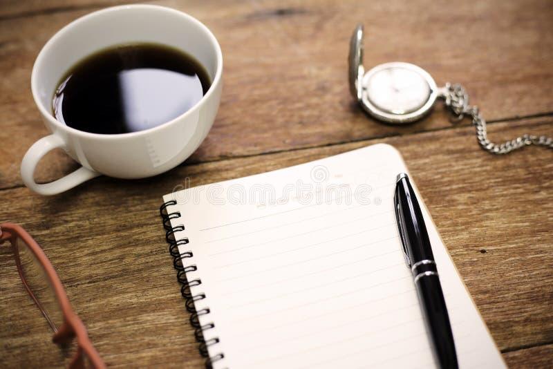Bästa sikt av kontorstabellen med koppen för penna för tomt papper för anteckningsbok royaltyfri fotografi