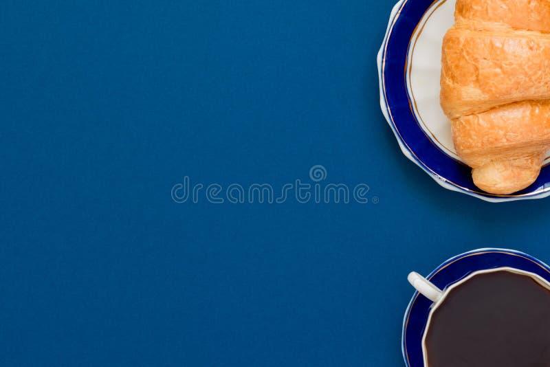 Bästa sikt av koppen av svart coffe och gifflet på en platta på blå bakgrund med kopieringsutrymme Morgonfrukost i fransk stil royaltyfri bild