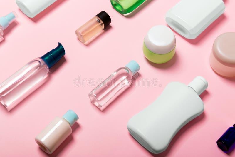 Bästa sikt av kosmetiska behållare, sprejer, krus och flaskor på rosa bakgrund Närbildsikt med tomt utrymme för din design arkivfoton