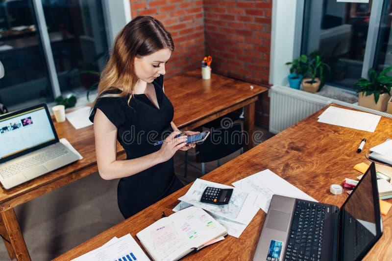 Bästa sikt av kvinnan som arbetar genom att använda smartphoneanseende på hennes arbetsplats i idérikt kontor arkivbild