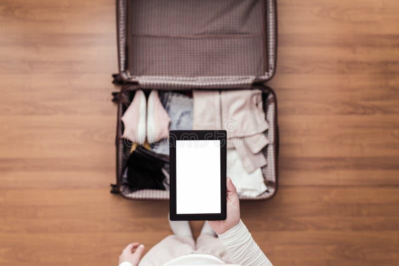 Bästa sikt av kvinnan som packar ett bagage för en ny resa Kvinnligt anseende ovanför resväskan med den elektroniska anteckningsb arkivfoto
