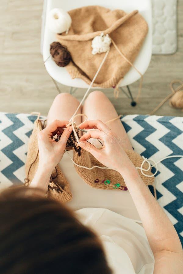 Bästa sikt av kvinnan som sticker den varma beigea tröjan på säng Gullig byrackahund förutom Hem-, frilans- handgjort lynnebegrep royaltyfri bild