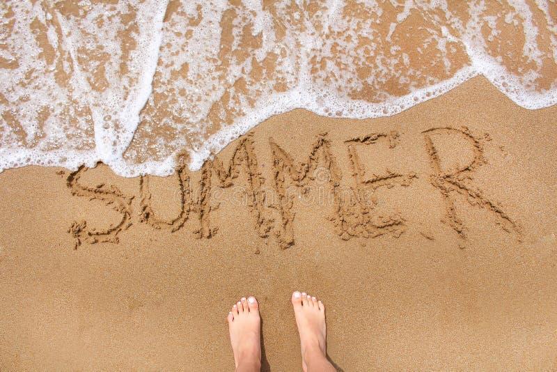 Bästa sikt av kvinnlig fot som står på strandsanden med att komma för vågrörelse Ordsommarhandstil på sanden Sommarlopp och arkivfoto