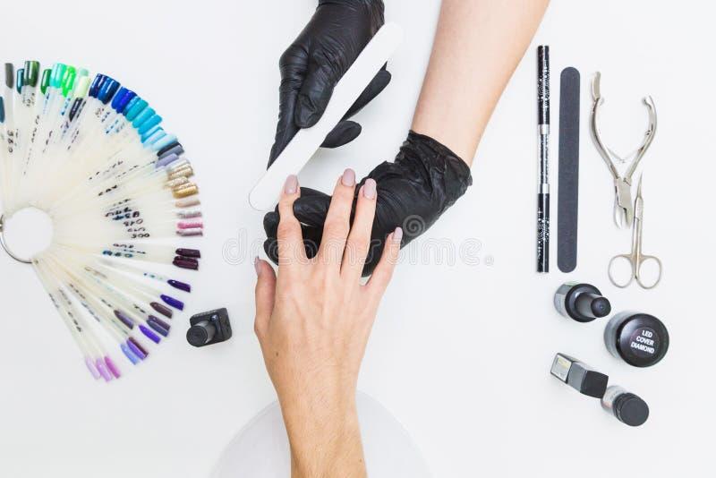 Bästa sikt av kvinnliga händer i en manikyrprocess på en vit tabellbakgrund med hjälpmedel för manikyr royaltyfria foton