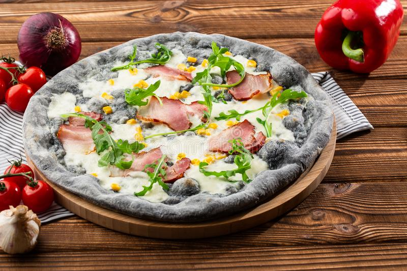 Bästa sikt av läcker pizza på trätabellen Smaklig pizza med skinka, havre, rucola och ost svart pizza arkivbilder