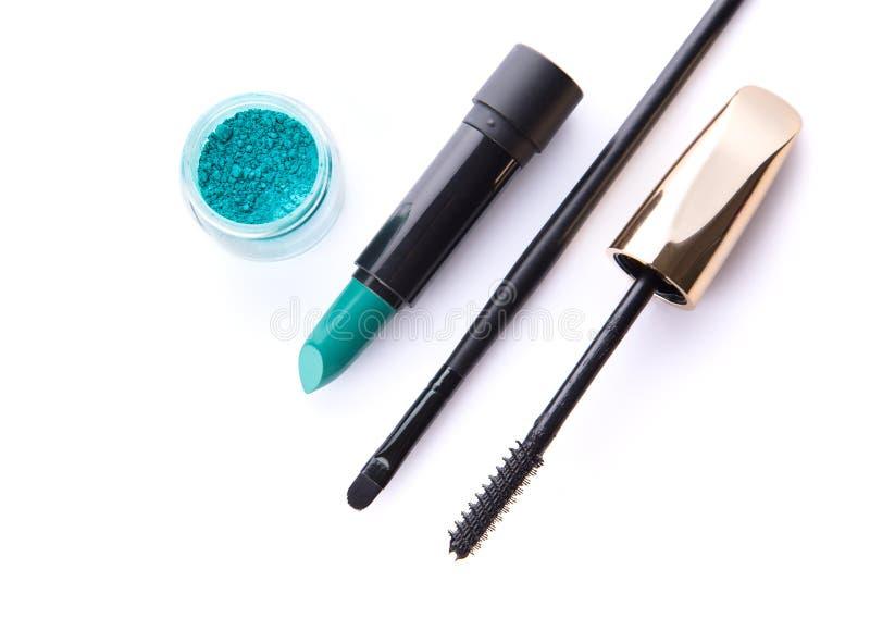 Bästa sikt av lös ögonskugga, läppstift, makeupborsten och mascar royaltyfri fotografi