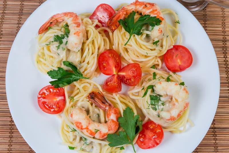 Bästa sikt av lagad mat spagetti med räkor och körsbärsröda tomater royaltyfri foto