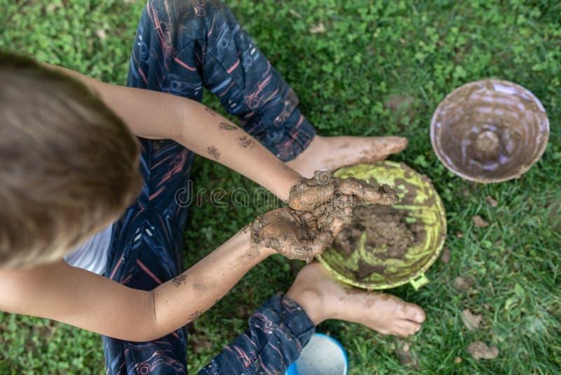 Bästa sikt av litet barnpojken som sitter på grönt gräs som spelar med gyttja arkivbild