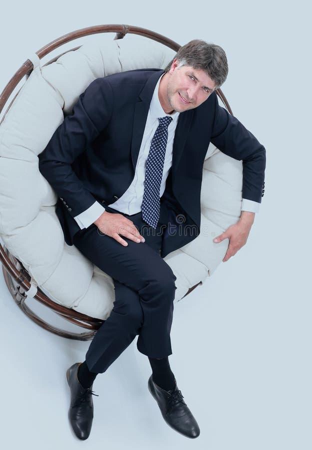Bästa sikt av lyckat affärsmansammanträde i bekväm stol arkivfoton