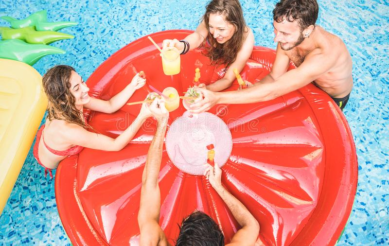 Bästa sikt av lyckliga vänner som dricker coctailar på simbassängpartiet - semesterbegrepp med lyckliga grabbar och flickor som h royaltyfri fotografi