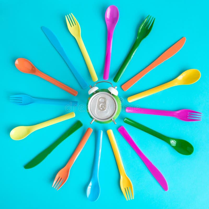 Bästa sikt av mångfärgade plast- skedar, gafflar och knivar med aluminiumburken i formen av ringklockan som isoleras på blått Mat royaltyfria bilder