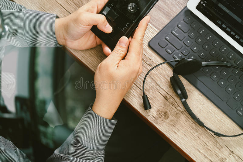 bästa sikt av manhanden genom att använda den VOIP hörlurar med mikrofon med digitalt minnestavlakomp royaltyfria foton