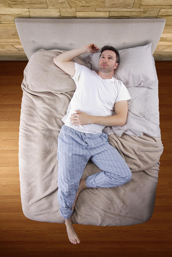 Bästa sikt av mannen på säng royaltyfri bild