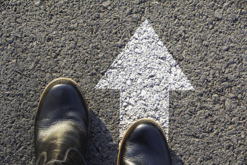 Bästa sikt av mannen som bär svarta skor som väljer en väg som markeras med vita pilar Väljer det högra banabegreppet arkivfoton