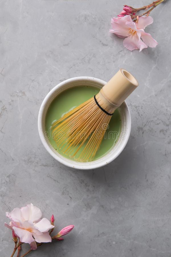 Bästa sikt av matchaen för grönt te i en bunke på grå färgmarmoryttersida med den härliga oleanderblomman fotografering för bildbyråer